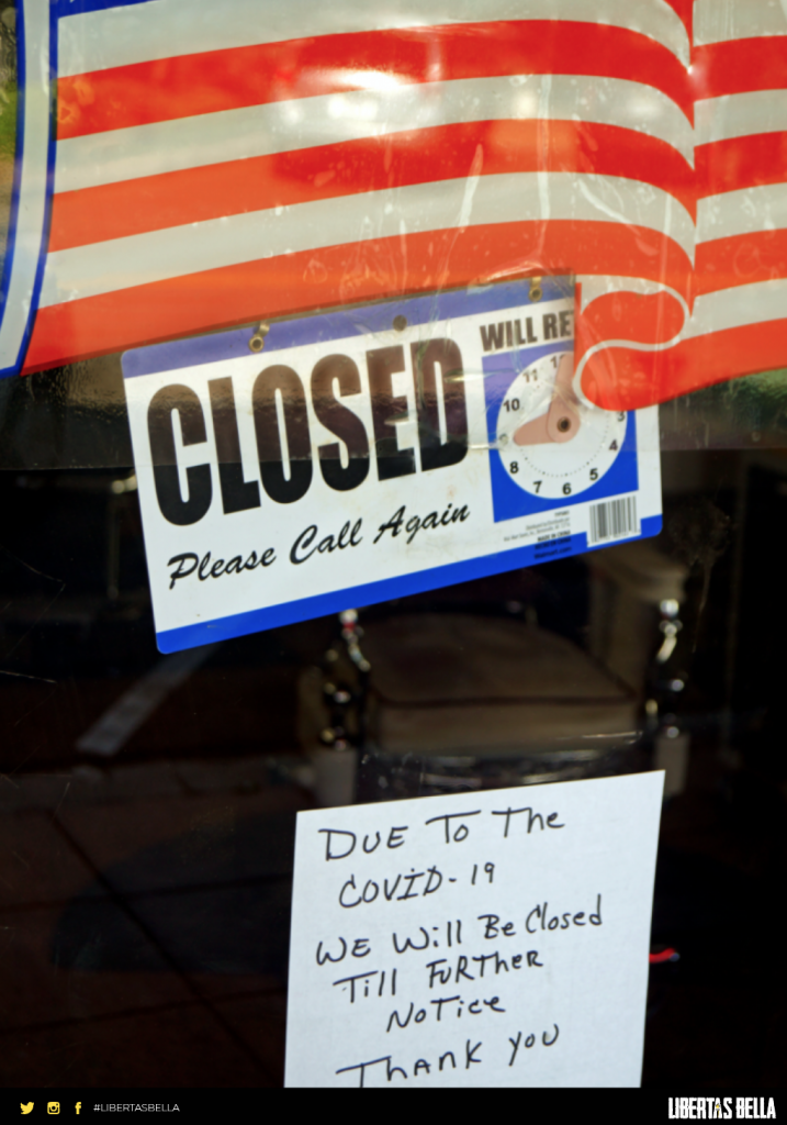 "COVID-19 lockdowns - glass door with USA flag and a sign that says ""Closed, Due to COVID-19 We will be closed til further notice"""