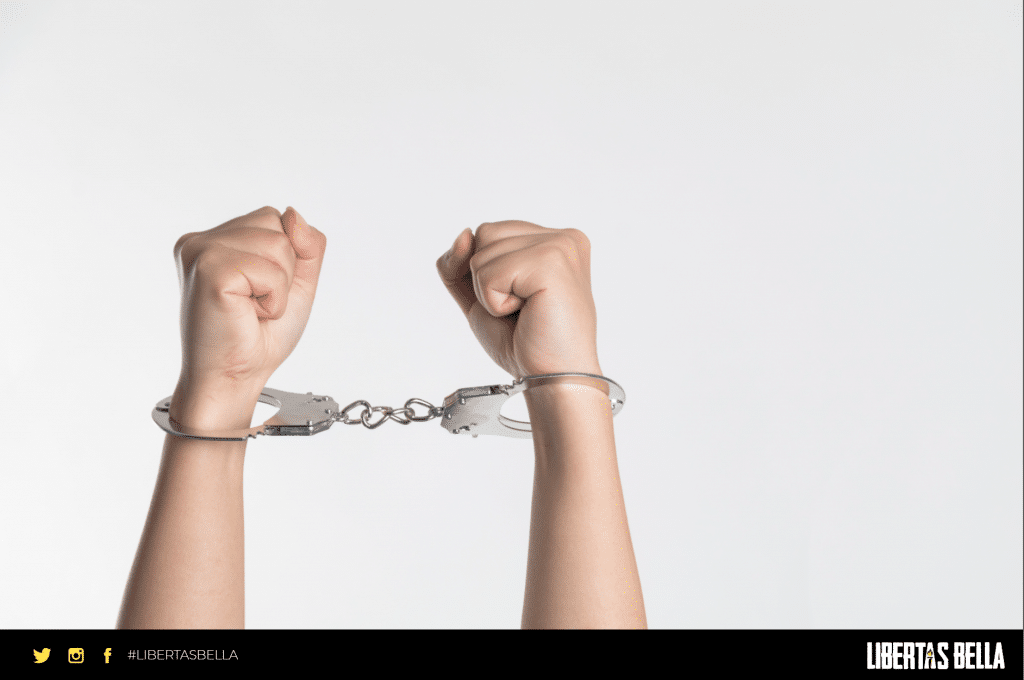 Tyranny quotes - two raised arms with handcuffs on